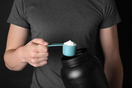 Man with scoop and jar of protein powder on black background, closeup