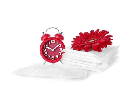 Menstrual pads, alarm clock and flower on white background. Gynecological care