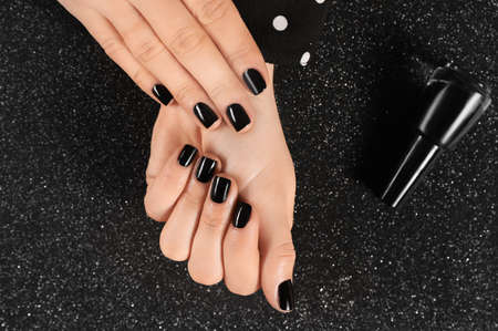 Woman with black manicure and nail polish bottle on dark background, top view