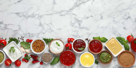 Flat lay composition with different sauces and space for text on marble background