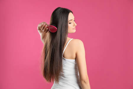 Beautiful young woman with hair brush on color background Reklamní fotografie