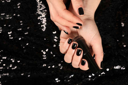 Woman with black manicure and nail polish bottle on dark background, top view. Space for text