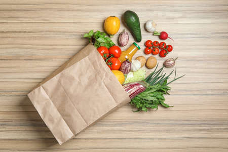 Overturned paper bag with vegetables, herbs and bottle of juice on wooden background, flat lay