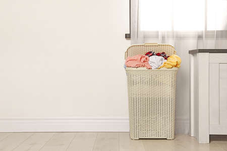 Plastic laundry basket full of dirty clothes on floor near light wall in room. Space for text Imagens - 124958114