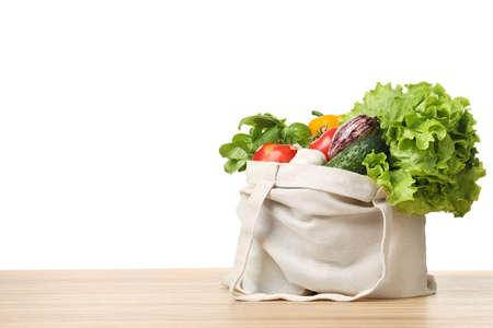 Stoffbeutel mit Gemüse auf dem Tisch vor weißem Hintergrund. Platz für Text