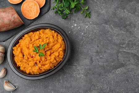 Flat lay composition with mashed sweet potatoes on grey background, space for text