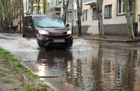 Car driving through large puddle outdoors on rainy day Banco de Imagens