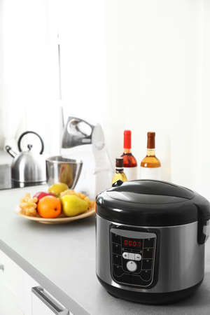 Modern multi cooker and products on table in kitchen. Space for text