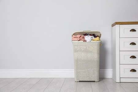 Plastic laundry basket with dirty clothes near light wall in room. Space for text Imagens - 124958151