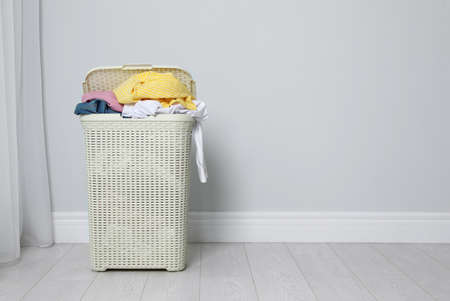 Plastic laundry basket full of dirty clothes on floor near light wall. Space for text Imagens - 124958183