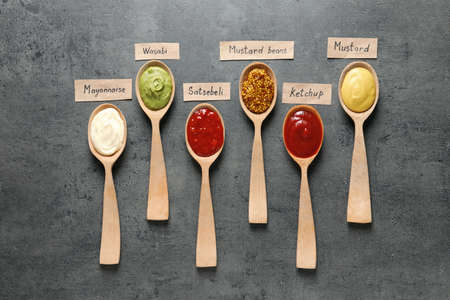 Different sauces in spoons and name tags on gray background, flat lay Stock Photo - 124958185