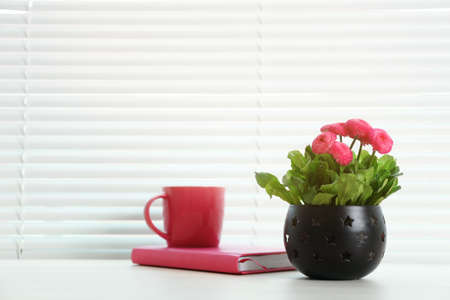 Window with blinds, beautiful potted plant, notebook and cup on sill, space for text
