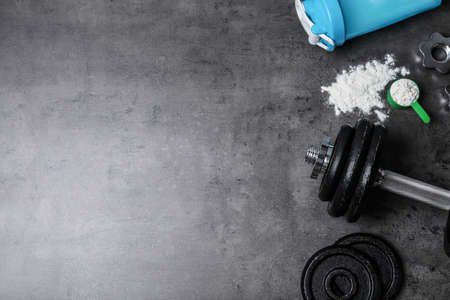 Flat lay composition with protein powder and fitness equipment on grey background. Space for text