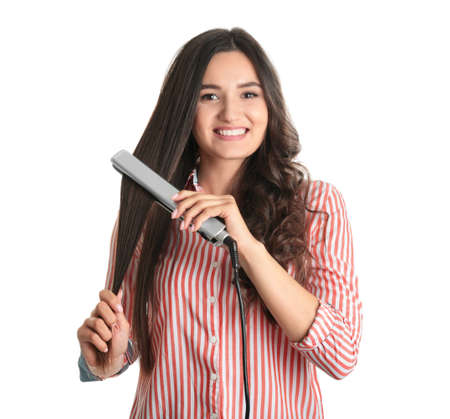 Young woman using hair iron on white background