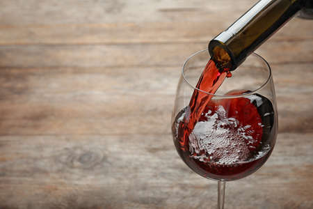 Pouring red wine from bottle into glass on wooden background. Space for text