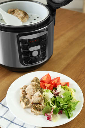 Delicious chicken with vegetables and modern multi cooker on wooden table