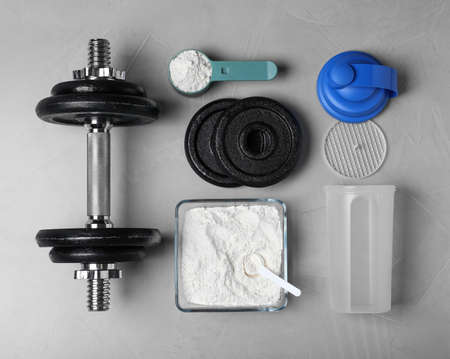 Flat lay composition with protein powder and dumbbell on grey background Stock Photo