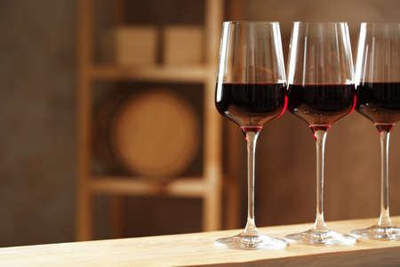 Glasses of red wine in cellar, space for text. Expensive drink