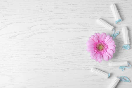 Flower and tampons on white wooden background, flat lay with space for text. Gynecological care