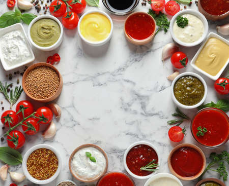 Frame made with different sauces and ingredients on marble background, flat lay. Space for text Stock Photo