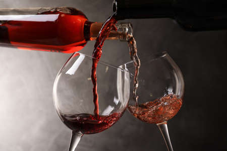 Pouring different wines from bottles into glasses on dark background Banco de Imagens