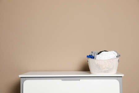 Plastic laundry basket with dirty clothes on chest of drawers near color wall. Space for text Imagens - 124958865