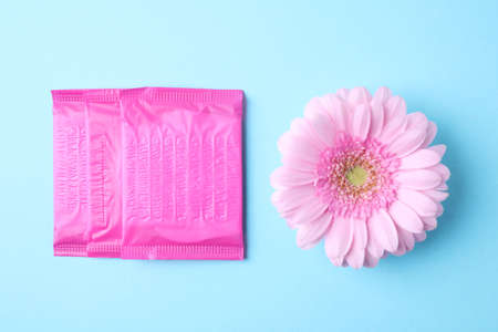 Packed menstrual pads and flower on color background, flat lay. Gynecological care