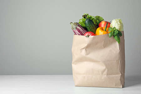 Paper bag with vegetables on table against grey background. Space for text