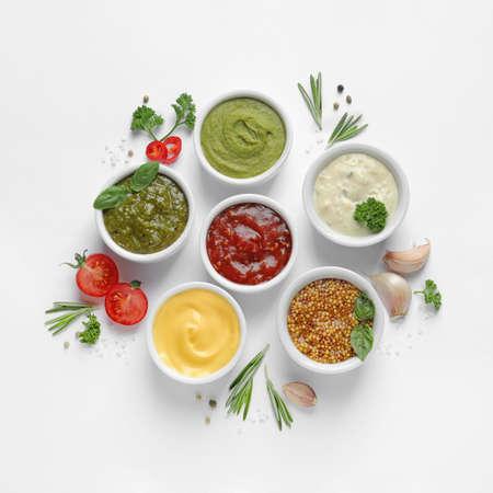 Composición con diferentes salsas e ingredientes sobre fondo blanco, endecha plana Foto de archivo
