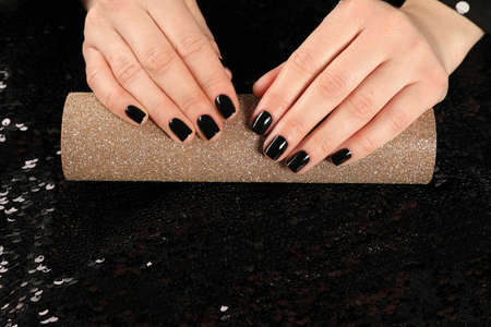 Woman showing black manicure on rolled shiny paper, closeup with space for text. Nail polish trends