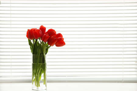 Window with blinds and beautiful bouquet on sill, space for text