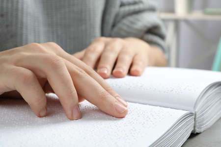 Blind person reading book written in Braille, closeup Imagens