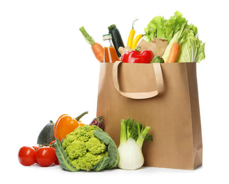 Paper bag with fresh vegetables and bottle of juice on white background Banco de Imagens
