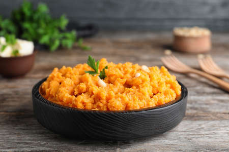 Plate with mashed sweet potatoes on wooden table