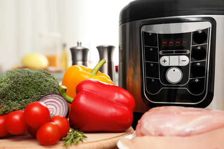 Modern multi cooker and products on table in kitchen, closeup. Space for text Фото со стока