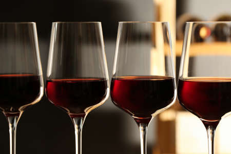 Glasses of red wine in cellar, closeup. Expensive drink Stok Fotoğraf
