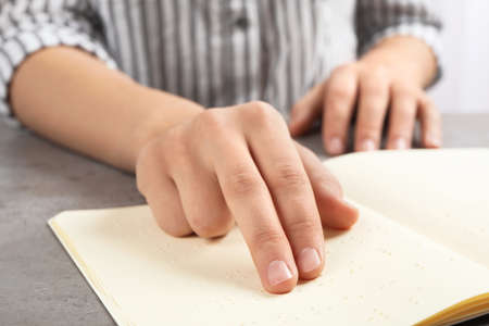 Blind person reading book written in Braille at table, closeup Imagens