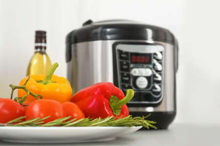 Modern multi cooker and products on kitchen table Imagens