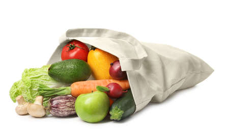 Overturned cloth bag with vegetables on white background