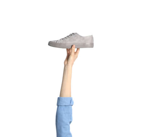 Woman holding sportive shoe on white background, closeup