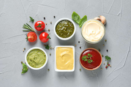 Flat lay composition with different sauces and ingredients on gray background Stock Photo