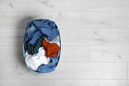 Laundry basket full of dirty clothes on floor, top view. Space for text Imagens - 124961036