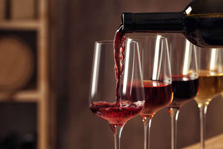 Pouring wine from bottle into glass in cellar, closeup