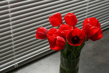 Bouquet of beautiful tulips in vase near window with blinds