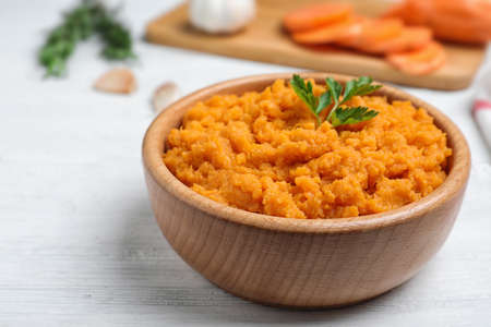 Bowl with mashed sweet potatoes on wooden table