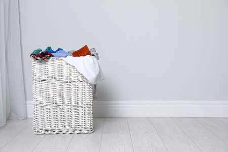 Wicker laundry basket full of dirty clothes on floor near light wall. Space for text Imagens - 124961167