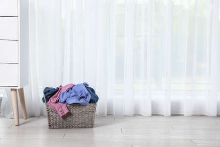 Wicker laundry basket with dirty clothes near window in room. Space for text Imagens - 124961194