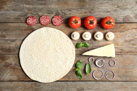 Flat lay composition with base and ingredients for pizza on wooden table Stock Photo - 124961240