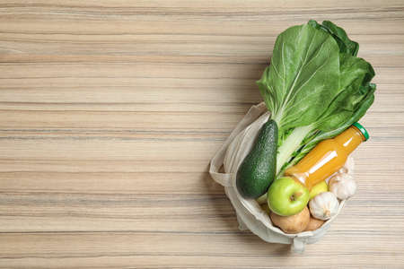 Cloth bag with fruits, vegetables and bottle of juice on wooden background, top view. Space for text
