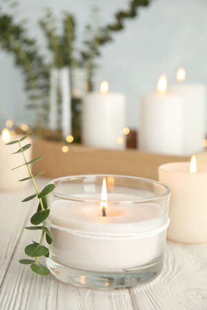 Burning aromatic candle and eucalyptus branch on table. Space for text Stock Photo